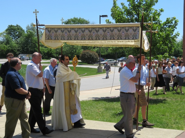 Father Raed Bader carries Blessed Sacrament